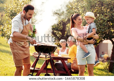 Barbecue time. Happy family make barbecue together in garden.