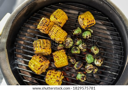 Barbecue vegetables. Grilling vegetables. Grilling corn and brussels sproutson a kamado grill. Grilled vegetable close up on a grill, top view. Homemade vegan barbecue, vegetarian barbecue and grill