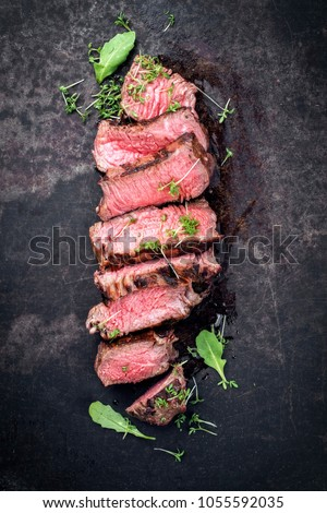 Barbecue wagyu point steak slices with lettuce and herbs as top view on a board with copy space