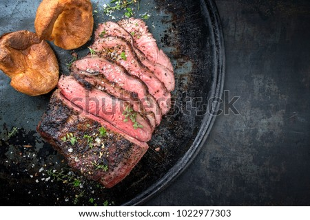 Barbecue wagyu roast beef sliced with Yorkshire pudding as top view on a tray with copy space right