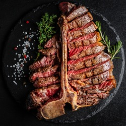 Barbecue Wagyu T-Bone Steak sliced. porterhouse grilled beef steak Medium rare on stone table. American meat restaurant. square image, top view.