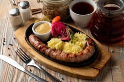 Barbecue wurst with potato and pickles, close up for a pub menu, wooden background, soft light