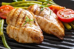 Barbecued chicken breasts on a grill pan with fresh green vegetable and chery tomatoes and rosemary twigs.