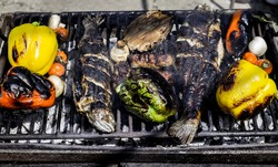 Barbecuing an assortment of red, yellow and green capsicum,  mushrooms, and trout fish