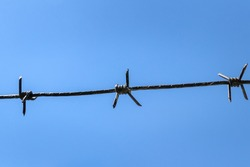 barbed wire against blue sky background. imprisonment and prison concept