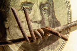 Barbed wire against blurred one hundred US Dollar bill as symbol of economic warfare, sanctions and embargo busting. Close up. Horizontal image.
