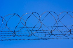 barbed wire and fence for security at airport or prison. blue sky in background