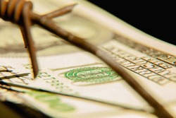 Barbed wire and US Dollar bill as symbol of economic warfare, sanctions and embargo busting. Selective focus.