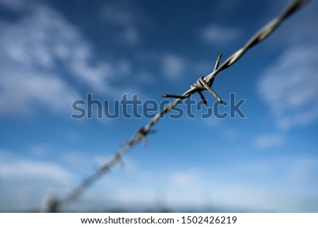 Barbed wire fence along the boundary line The background is blue sky.shallow focus effect. #1502426219