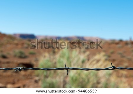 barbed wire fence made of steel in front of desert and blue sky in the USA