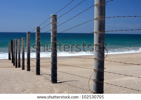 Barbed wire fence on a beach