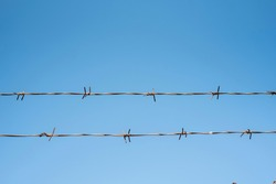 Barbed wire fence over blue sky