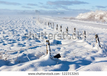 Barbed wire fence, road with snow covered ground and fog