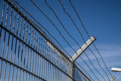barbed wire fence too keep out burglars from home and keep in prisoners in imprisonment