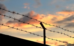 Barbed wire fence with Twilight sky to feel Silent and lonely and want freedom.