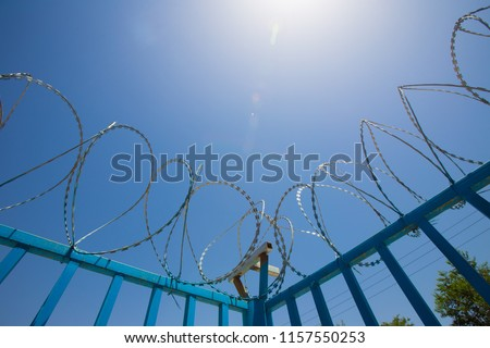Barbed wire fencing. Blue Fence made of wire with spikes on top to prevent area from dangerous outsider #1157550253