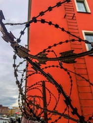 Barbed wire fencing to prevent entry into the protected area. Barbed wire on the background of a red building.