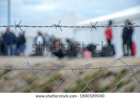 Barbed wire in refugee camp. Migrants behind chain link fence in camp. Group of people behind fence. Concept of prison, freedom, barrier, security and migration. Refugees on their way to EU. Foto stock ©