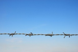 Barbed wire on a fence, with a blue sky background