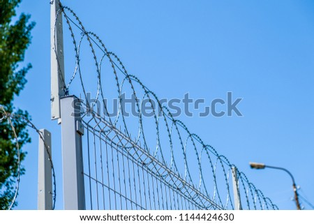 Barbed wire on a wire fence. #1144424630