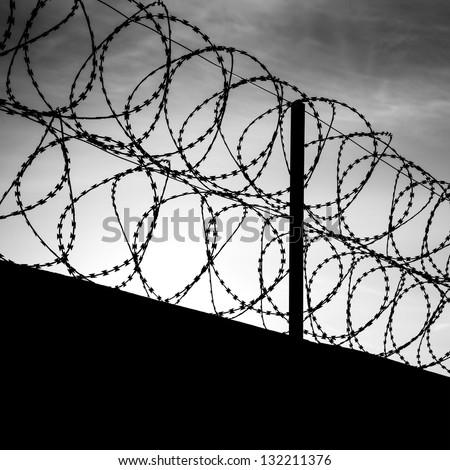 Barbed wire on dark fence. Monochrome silhouette photo