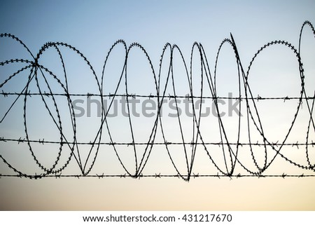 Barbed wire on dark fence. Monochrome silhouette photo, The tangle barb with blue sky