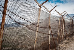 Barbed wire on fence of a private area around Israeli settlements on Golan heights, Israel. Protective fencing of specially protected object of barbed wire. Stamped barbed wire.