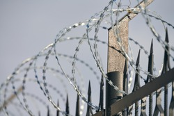 Barbed wire on fence, steel grating fence, metal fence wire. Coiled razor wire with sharp steel barbs on top of wire mesh perimeter fence. Private area, safety and security concept.