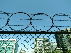 Barbed wire on fence top surrounding urban buildings