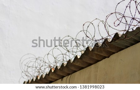 Barbed wire on security boundary wall with rusted metal roof #1381998023