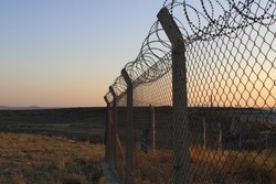 Barbed wire on sunset. Spiky wire fence. Prison barbed fence. Airport security fence after sunset. National border. Barbed Wire Fence in a military base. Area with barbed wire. Dangerous area.
