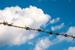 Barbed wire on the blue sky with clouds background.