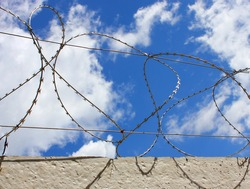 Barbed wire on the concrete fence protecting the industrial enterprise. Against the blue sky