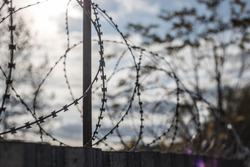 Barbed wire on the fence. The concept of prison, rescue, refugee, solitude. Background, not focus