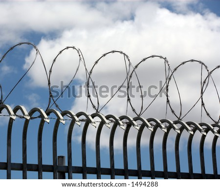 Barbed wire on top of wrought iron fencing