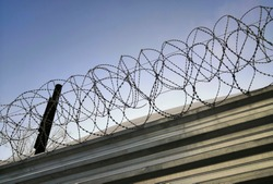 Barbed wire over a metal fence against the sky. Barbed wire on the prison fence