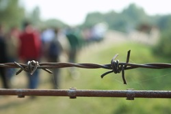 barbed wire with blurred shapes of migrants