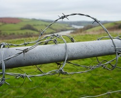 Barbed wire wrapped around farmyard gate with hills and river in the distance
