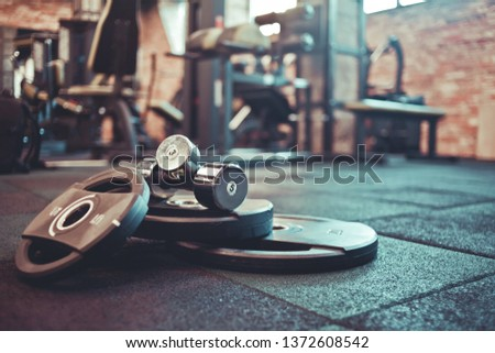 Barbell, dumbbells lie on the floor against the background of the gym. Free weight training. Functional powerful training
