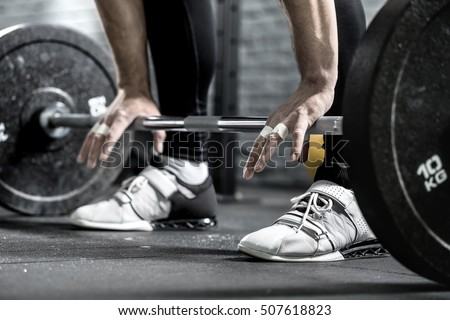 Barbell on the floor and the man's hands on it on the background of guy's legs in the black pants and white sneakers. Close-up horizontal photo.