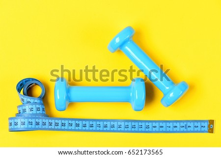barbell or dumbbells and measuring tape on yellow background, aerobics concept #652173565