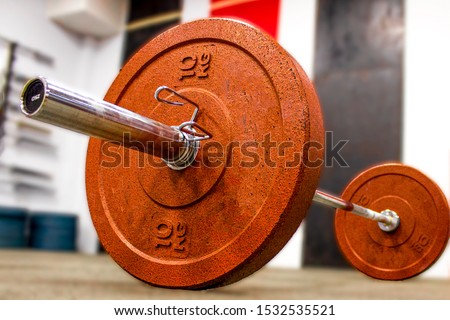 Barbell with red weight plates 10 kg for crossfit training and metal locks, in the hall. Blurred background. Close up.