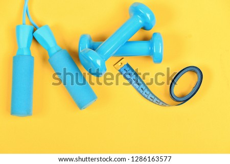 Barbells and skipping rope next to measure tape roll. Sports and healthy lifestyle concept. Dumbbells and jump rope in cyan color isolated on yellow background. Shaping and fitness equipment, top view #1286163577