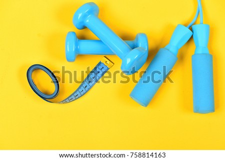 Barbells and skipping rope next to measure tape roll. Sports and healthy lifestyle concept. Dumbbells and jump rope in cyan color isolated on yellow background. Shaping and fitness equipment, top view #758814163