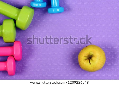 Barbells in pink, green and blue colors near apple fruits, top view. Dumbbells and apples on purple texture background, copy space. Shaping and fitness equipment. Healthy shape and sport concept #1209226549