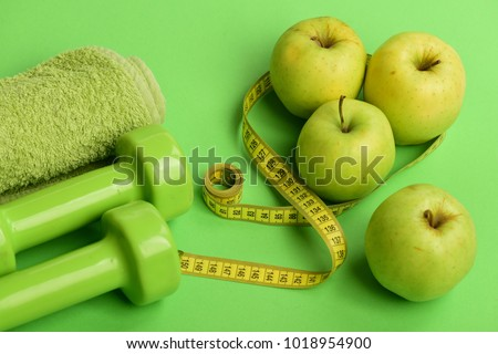 Barbells made of plastic near juicy green apples. Diet and sport regime concept. Dumbbells in bright green color, measure tape, towel and fruit on green background. Sports and healthy regime equipment