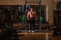 Barbells workout. Bodybuilder athletic man with six pack, perfect abs, shoulders, biceps, triceps, chest. Athletic guy standing with barbell, workout in gym. Muscular man workout with barbell at gym.