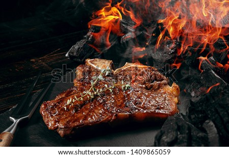 barbeque steak on a black slate board with meat fork and grill coals next to it