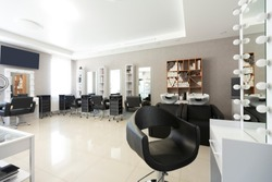 Barber chair for client on front background at interior of beauty salon
