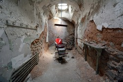 Barber Chair Under a Skylight in an Old Abandoned Stone Prison Cell